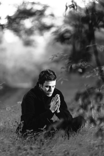 grayscale-photography-of-man-sitting-on-grass-field-156151